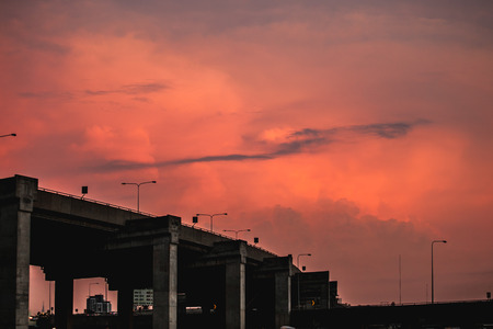 silhouette express way bridge after working on orange sky in twilight time