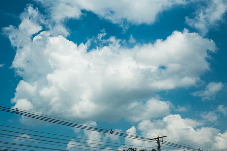 nice blue sky shaggy white clouds with electric lines and pole