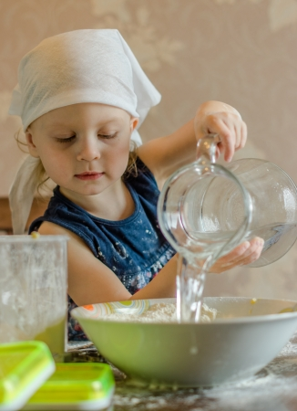 child knead the dough in a kerchief photo