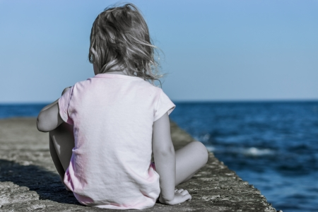 One child sits and watches quietly in a serene sea photo