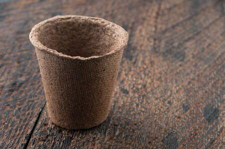turba: Una turba Macetas en es el fondo de madera Foto de archivo
