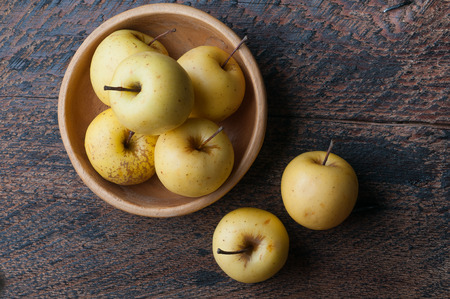 granny smith apple: a few green apples in a wooden bowl on the table
