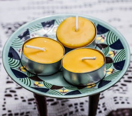Three tea candles on colorful stool Stok Fotoğraf