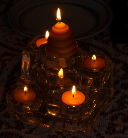 Lit arranging candles in dark room