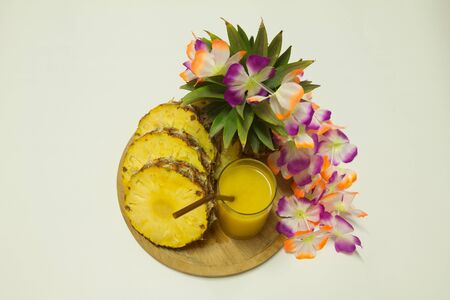 Pineapple juice, flowers, and a slice of pineapple isolated on white  photo