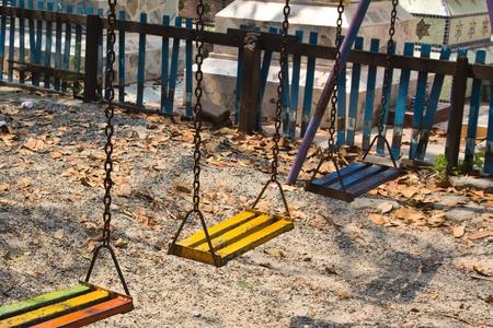 Empty baby swings on summer playground