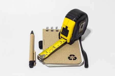 black tape measure accessories, notebook, pen on background white   photo