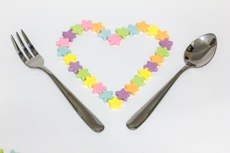 Candy hearts ,with spoon and fork on white