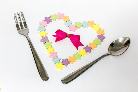 Candy hearts ,with spoon and fork on white background