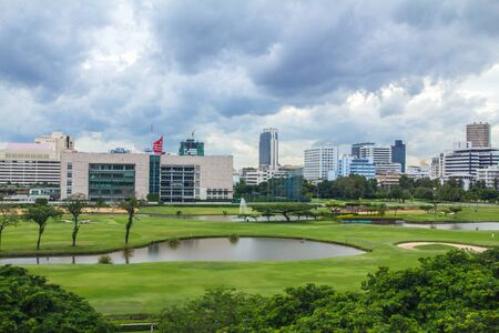 The landscape of golf courses in Bangkok, a retail district dominated by towers and skyscrapers, surrounds. Stock Photo