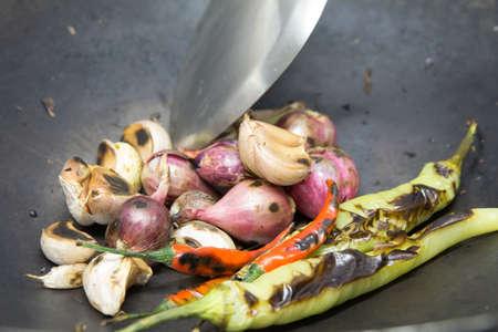 roasting pan: Shallots, garlic, chili, food ingredients grilled on the pan.