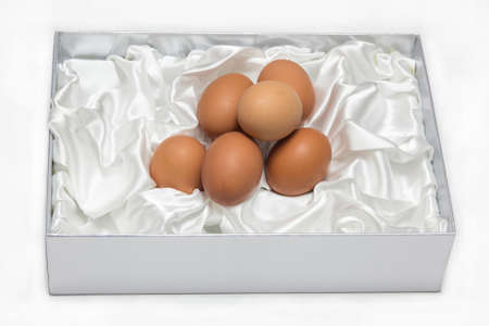 upholstered: Eggs in the box decorated with white cloth on white backgroung.