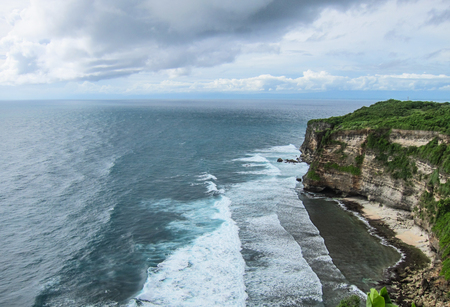 Steep cliffs on the beach with the blue sea of Uluwatu in Bali. Stock Photo