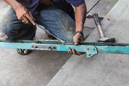 Closeup on mans hand, repair the Iron door. working outdoors. Stock Photo