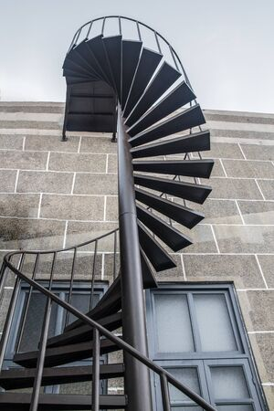 outside, metal brown spiral staircase and gray window on  wall of cement Stock Photo