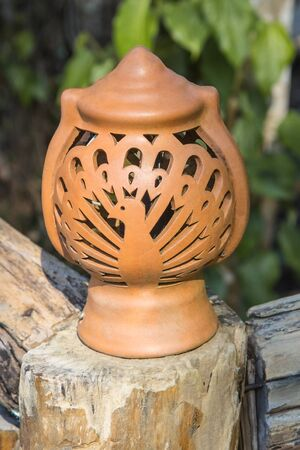 Brown pottery lamp is located on a garden walkway.