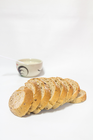 Cereal bread mixed with white sesame seeds, sprinkle with oatmeal, soy milk in a ceramic cup and spoon.