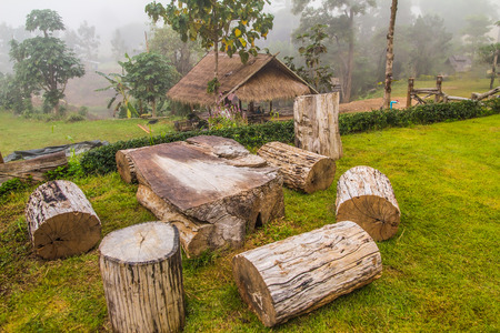 The nature of the cross section of trees. Made of wooden bench and table made of trunks tree is placed on the tourist trail