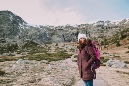 Brunette girl with a hat on her head and a travel backpack contemplates the landscape that surrounds her from a valley next to the mountains Banco de Imagens