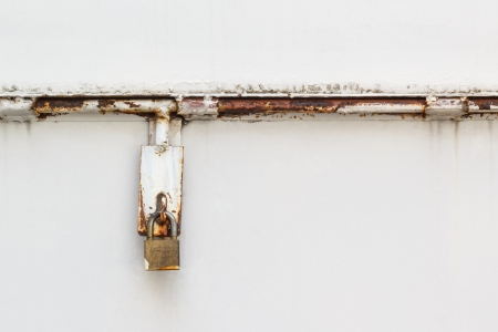 Old rusty padlock on white wall photo