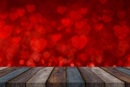 Empty wooden deck table on red background with heart shape. Valentines day concept