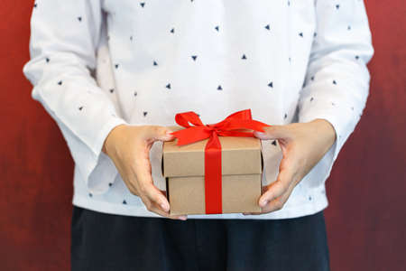Female hands holding a gift wrapped with red ribbon