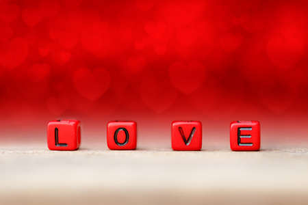 Red block cube with love word on wood table. Red blur background with heart shape. Concept of valentine day