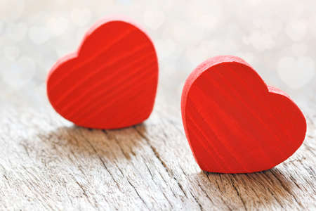 Two small red hearts made of wooden on bright white lights bokeh background. Valentine day background