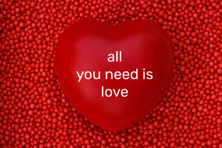 Red heart with all you need is love word on red foam beads background. Concept of valentine day