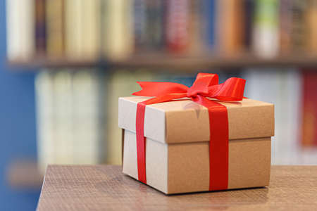 Gift box with red ribbon bow on wooden background