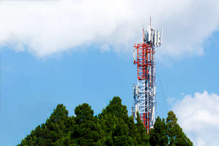 Communication transmitter tower with antenna on blue sky background