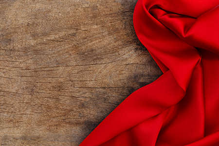 Red satin fabric on brown wood background. Valentines day background Фото со стока