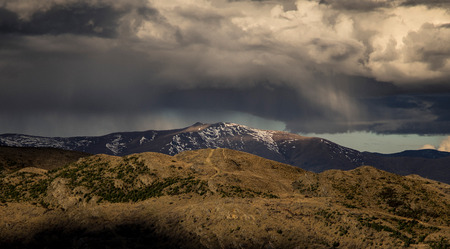 dramatic rain storm cloud form over the snow mountain in New Zealand