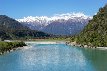 New Zealand scenery, mountains with snow on the top with turquoises riverfront in forest and blue sky in background