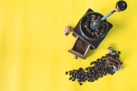 coffee beans and grinded coffee bean in vintage wooden coffee grinder on yellow background