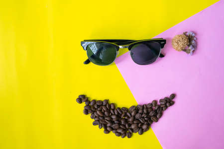 top view flat layer funny face made from coffee beans in smile icon shape , wooden grinder basket and sun glasses on two tone multicoloured background