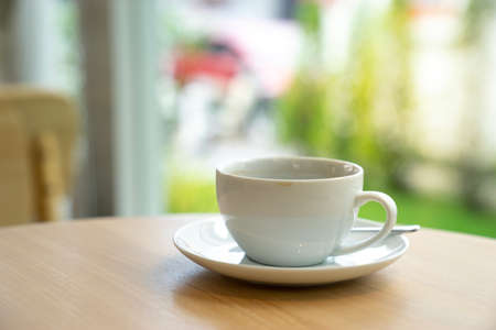 white coffee cup on wooden table with coffee shop background.