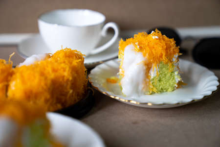 """close up selective focus piece of Gold Egg Yolk Thread Cake , or 'Cake Foi Tong"""" Thai pandan cake with delicious young coconut cream on white plate with blurred white coffee cup in background copy space"""
