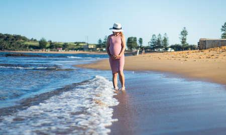 a pregnant woman in pink dress holding her belly and walking on the beach, coast line beach. Standard-Bild