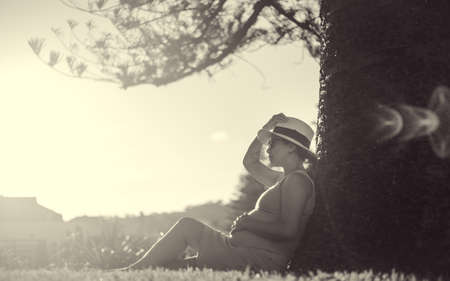 monotone a pregnant woman in pink dress sitting under big tree in warm evening summer