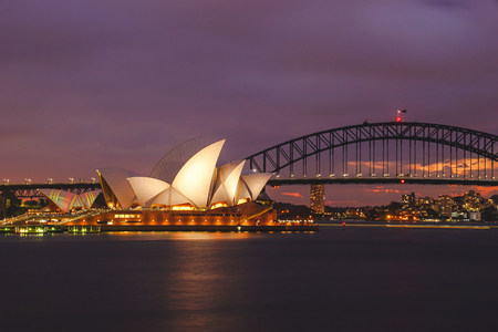 Opera House and Harbour Bridge at twilight in Sydney. The structures are considered as the major landmark of Sydney and tourists attraction. Editorial