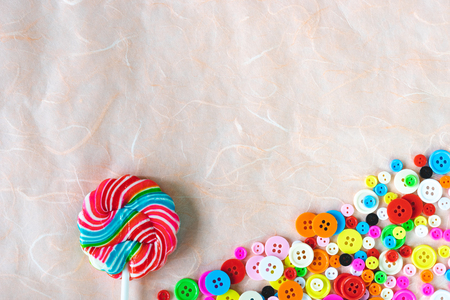 colourful buttons and  swirl lollipop on pink mulberry paper Stock Photo