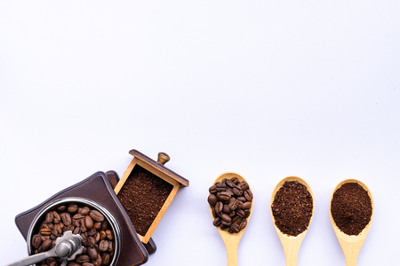 wooden spoons filled with coffee bean and crushed ground coffee , wooden grinder on white background, top view
