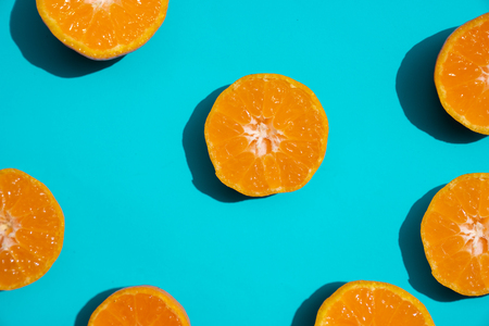 Top view fresh orange slices on bright blue background. Copy Space. creative summer concept. Half of citrus in minimal, Banner