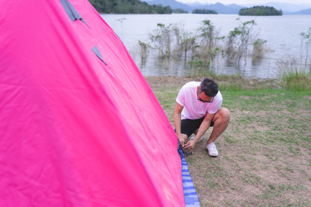 an asian man setting pink tent at campground