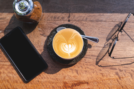 top view of cup of hot milk coffee with latte art, smartphone, eye glasses and brown sugar on wooden desk in the morning light