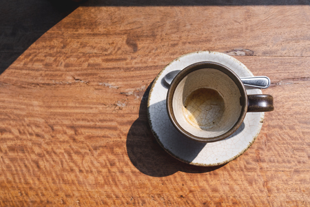 top view of empty coffee ceramic cup on wooden desk with morning light Imagens