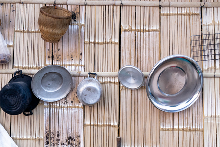 basic thai kitchen  cooking utensils hung on traditional wood  wall