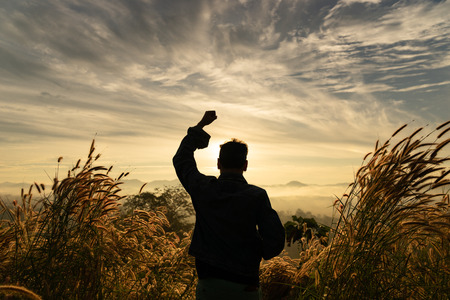 Silhouette man happy standing  with hands rise up on mountain with sunrise sky.   Man wanderlust nature standing open arms enjoying sun concept