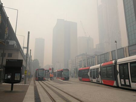 smoke haze from bush fire in NSW Sydney, covered trams and business building  at Circular Quay station in the afternoon, caused Sydneys air quality plummets. Australia. 10-12-2019